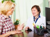 Älterer Doktor, der positive Nachrichten für einen Patienten hat Lizenzfreie Stockfotos