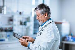 Älterer Doktor, der seinen Tablet-Computer bei der Arbeit verwendet Stockfoto
