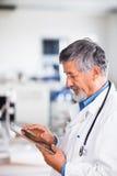 Älterer Doktor, der seinen Tablettecomputer verwendet Stockfotos