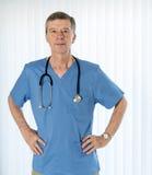 Älterer Doktor scheuert herein das Gegenüberstellen der Kamera stockfotos