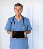 Älterer Doktor scheuert herein das Gegenüberstellen der Kamera stockfoto