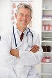 Älterer Doktor in Sprechzimmer Stockfotos