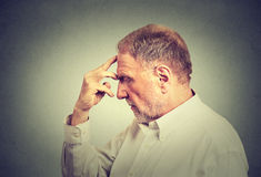 Älterer durchdachter Mann lokalisiert auf grauem Wandhintergrund Stockbild