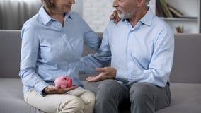 Älterer Ehemann und Frau auf Couchholdingsparschwein, zuverlässige Ablagerung, Bankwesen stockbild