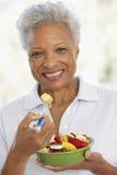 Älterer Erwachsener, der einen frischen Fruchtsalat isst Lizenzfreie Stockfotografie