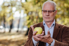 Älterer Erwachsener, der grünen Apfel hält Lizenzfreie Stockfotos
