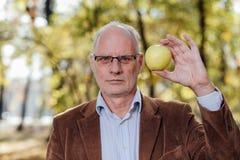 Älterer Erwachsener, der grünen Apfel hält Lizenzfreie Stockbilder