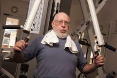 Älterer erwachsener Mann, der in der Gymnastik ausarbeitet. stockfotografie