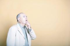 Älterer erwachsener Mann mit seiner Hand auf seinem Kinn, das oben neugierig schaut  Lizenzfreie Stockfotografie