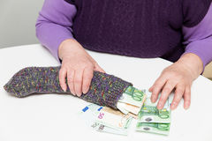 Älterer Erwachsener mit ihren Einsparungen in einer Socke lizenzfreies stockbild