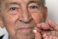 Älterer Erwachsener mit Medizinpille Stockfotos
