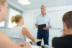 Älterer Erzieher, der mit Klassenjungeerwachsenen spricht Stockfotos