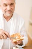 Älterer fälliger Mann, der Frühstücktoast isst Stockfotografie