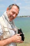 Älterer Fotograf durch die Küste stockfoto