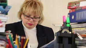 Älterer Frauenbuchhalter in den Gläsern und mit Handelsblättern stock video footage