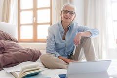 Älterer Frauenfreiberufler in ihrer Studie mit Computer Stockfotografie