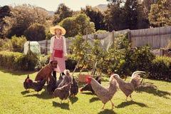 Älterer Frauenlandwirt mit ihrem Hund und Hühnern im Hinterhof lizenzfreie stockfotografie