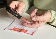 Älterer Frauenprüfungs-Blutzucker mit glycometer Stockfotos