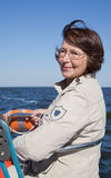 Älterer Frauensportsegler auf einer Segeljacht Stockfotos