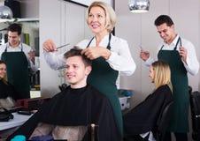Älterer Friseurumhüllungsjugendlicher Stockfoto