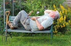 Älterer Gärtner, der auf dem Job schläft. Stockbild