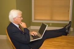 Älterer Geschäftsmann auf Laptop Lizenzfreie Stockfotos