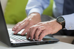 Älterer Geschäftsmann benutzt Laptop für Arbeit lizenzfreie stockfotos