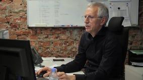 Älterer Geschäftsmann, der am Computer sitzt in seinem Büro arbeitet stock footage