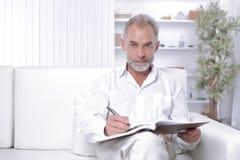 Älterer Geschäftsmann, der eine Anmerkung im Arbeitsbuch macht lizenzfreies stockfoto