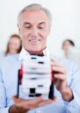 Älterer Geschäftsmann, der eine Visitenkartehalterung anhält Lizenzfreie Stockfotos