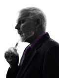Älterer Geschäftsmann, der elektronisches Ezigarettenschattenbild raucht Stockfotos