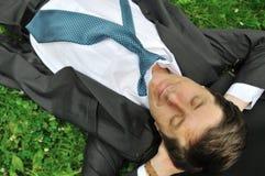 Älterer Geschäftsmann, der im Gras liegt Stockfotografie