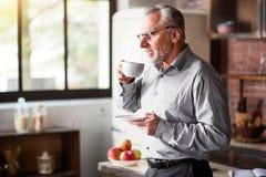 Älterer Geschäftsmann, der Kaffee in der Küche zu Hause trinkt stockfotografie