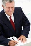 Älterer Geschäftsmann, der Kenntnisse im Büro nimmt Lizenzfreies Stockfoto