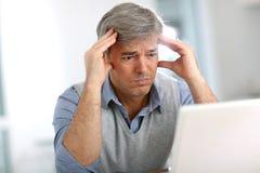 Älterer Geschäftsmann, der Kopfschmerzen hat Lizenzfreie Stockfotos