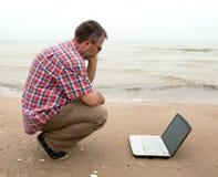 Älterer Geschäftsmann, der mit Notizbuch auf Strand sitzt Stockfotografie