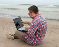Älterer Geschäftsmann, der mit Notizbuch auf Strand sitzt Stockfotos