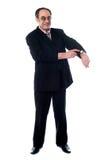 Älterer Geschäftsmann, der in Richtung zur Armbanduhr zeigt lizenzfreie stockfotos