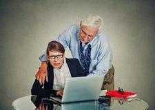 Älterer Geschäftsmann, der seine junge Kollegefrau bedrängt lizenzfreie stockfotografie