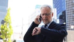 Älterer Geschäftsmann, der um Smartphone in der Stadt ersucht stock footage
