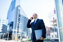 Älterer Geschäftsmann, der um Smartphone in der Stadt ersucht Lizenzfreie Stockbilder