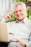Älterer Geschäftsmann, der zu Hause arbeitet Stockbild