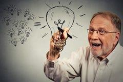 Älterer Geschäftsmann hat eine Idee, die eine Glühlampe mit Stift zeichnet Stockfotos