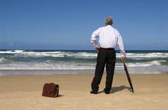 Älterer Geschäftsmann im Ruhestand, der von der Ruhestandsfreiheit auf einem Strand träumt Lizenzfreies Stockfoto
