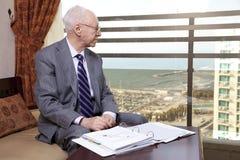 Älterer Geschäftsmann Looking Out das Fenster Lizenzfreie Stockfotos