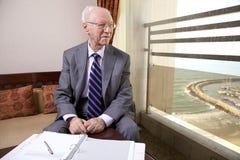 Älterer Geschäftsmann Looking Out das Fenster Lizenzfreies Stockfoto