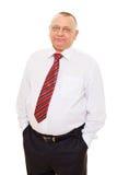 Älterer Geschäftsmann mit den Händen in den Taschen Stockbild
