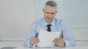 Älterer Geschäftsmann Reading Documents im Büro, Vertrag stock video footage