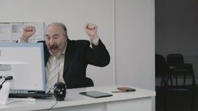 Älterer Geschäftsmann sehr freut sich am PC und ruft Arbeitskräfte 4K aus stock video