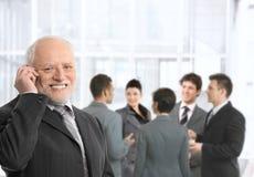 Älterer Geschäftsmann am Telefon in der Bürovorhalle Lizenzfreies Stockfoto